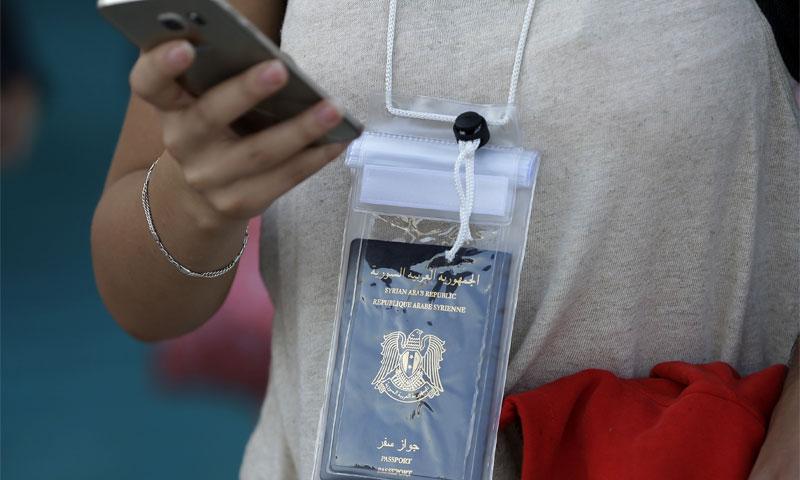 لاجئة سورية تحمل جواز سفرها (AP)