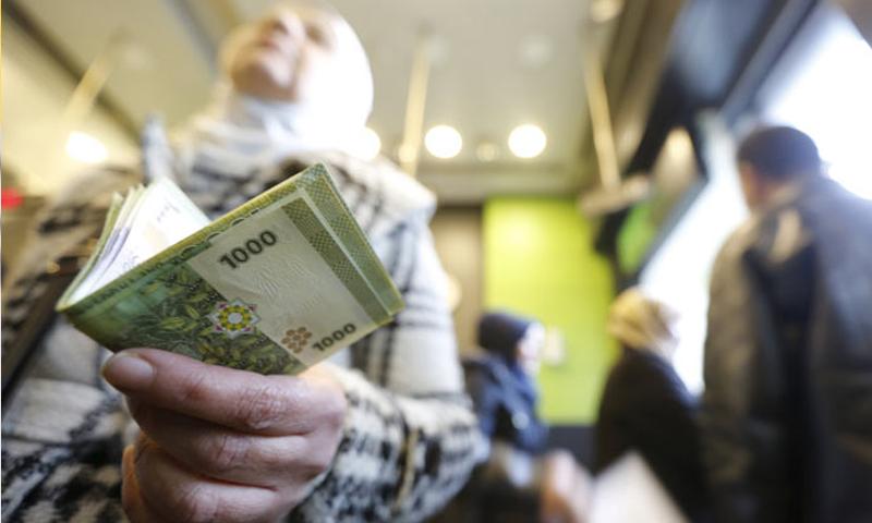 سيدة سورية تحمل عملة سورية من فئة الف ليرة (الوطن)