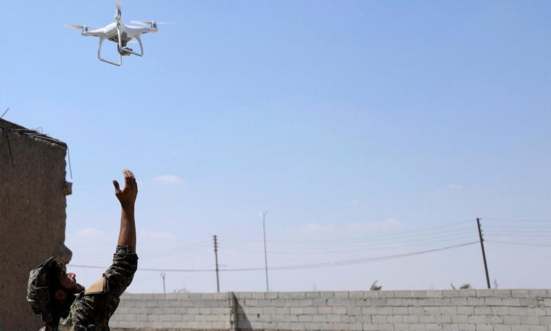 مقاتل من قوات سوريا الديموقراطية يسير طائرة استطلاع داخل أحياء مدينة الرقة - (رويترز)