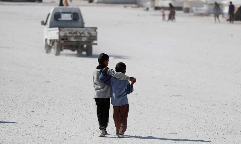 طفلان يسيران خلف سيارة في مخيم عين عيسى شمال سوريا - 14 تموز 2017 - (رويترز)