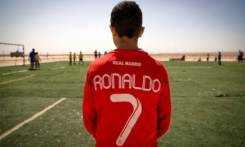 "طفل سوري يرتدي قميصًا كتب عليه ""رونالدو"" (SaveTheChildren)"