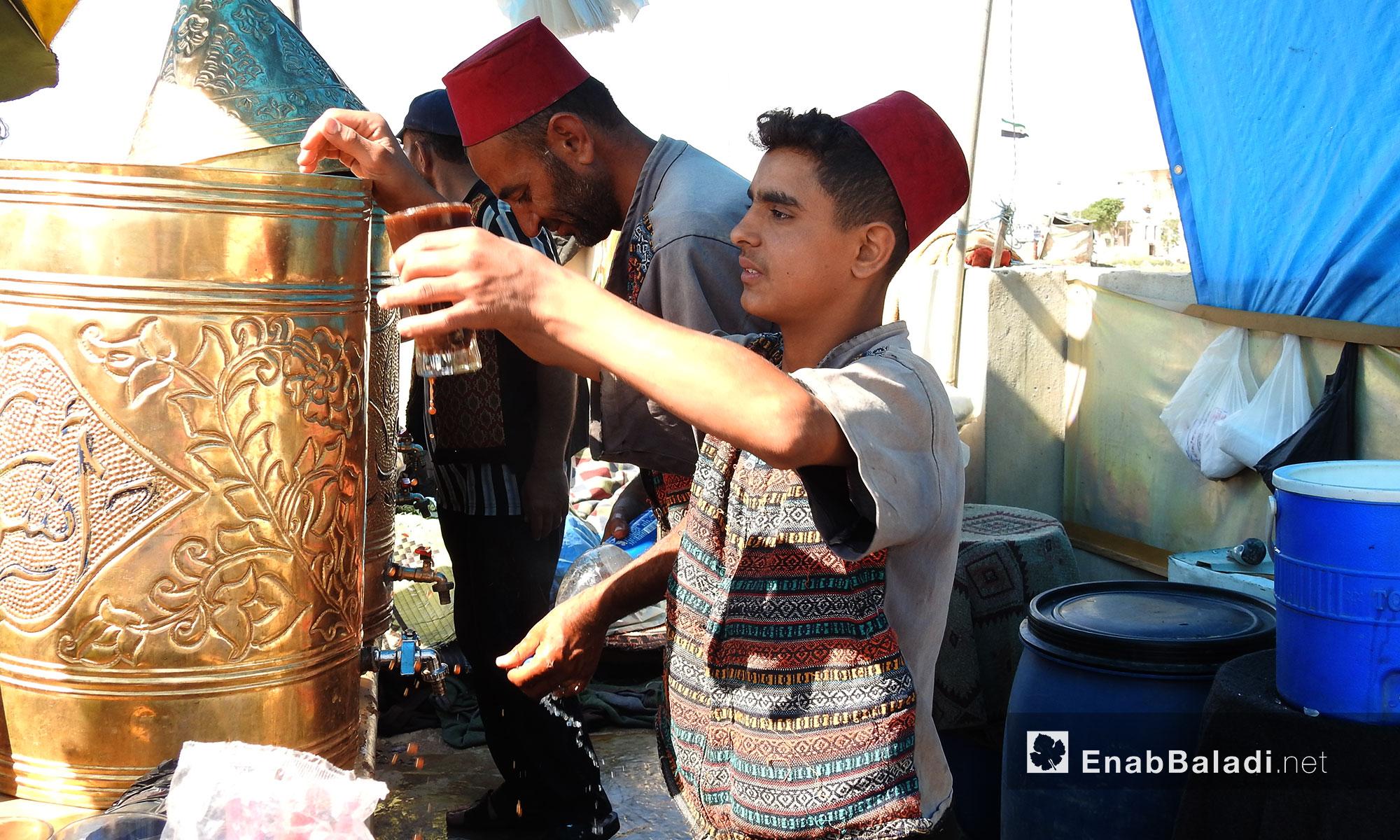 إقبال على بائع مشروبات شعبية باردة بالتزامن مع موجة الحر في قرية سجو بريف حلب الشمالي - 6 تمور 2017 (عنب بلدي)