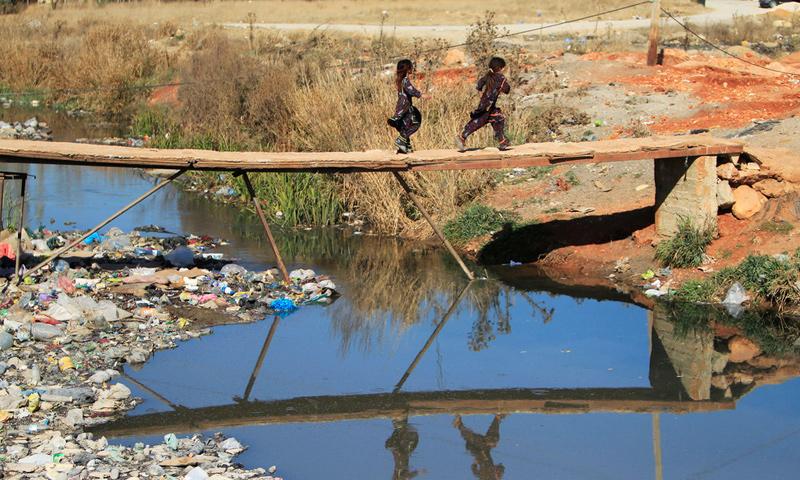 طفلان سوريان يعبران فوق نهر الغزال المليء بالقمامة في وادي البقاع في لبنان - 27 كانون الثاني 2017 - (رويترز)