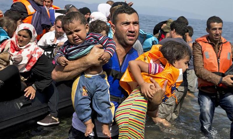 لاجئون سوريون بعد وصولهم من تركيا إلى جزيرة ليسبوس اليونانية - (AP)
