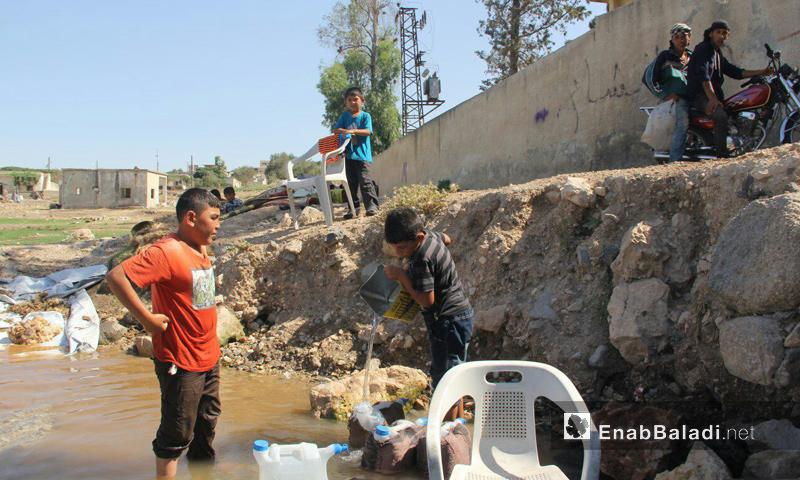 أطفال وأهالي بلدة قليدين في سهل الغاب بريف حماة يعبئون المياه - 9 تموز 2017 (عنب بلدي)
