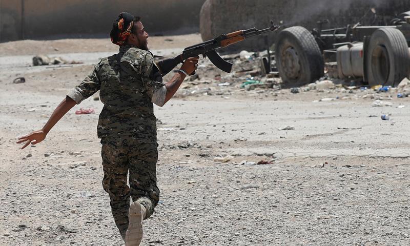 مقاتل من قوات سوريا الديموقراطية خلال المواجهات العسكرية مع تنظيم الدولة في مدينة الرقة - حزيران 2017 - (رويترز)