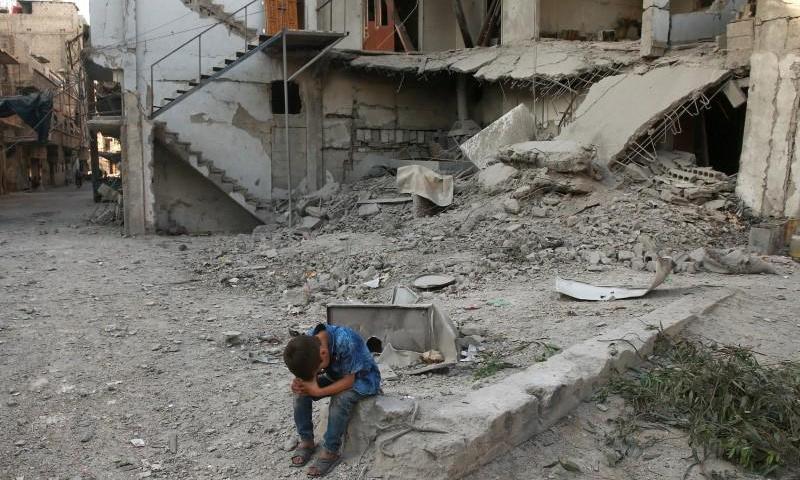 طفل يجلس بالقرب من منزل مدمر في مدينة عربين في الغوطة الشرقية - 7 آب 2017 - (رويترز)