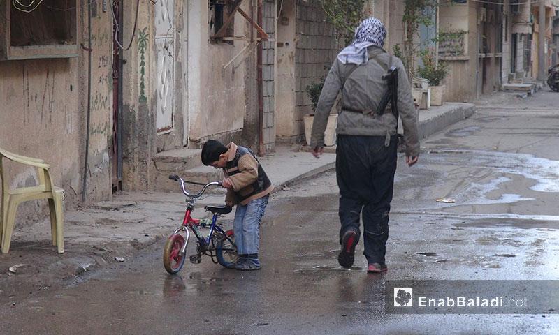 طفل مع مقاتل حي الشيخ ياسين في دير الزور - 2013 (عنب بلدي)