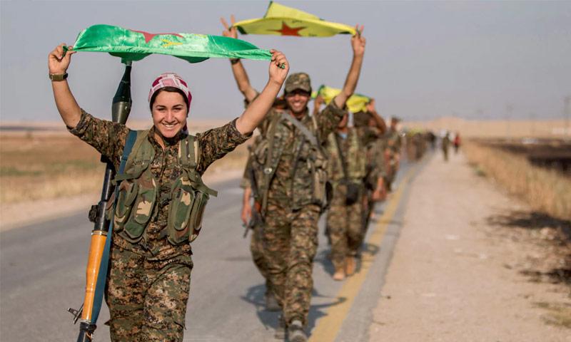 تعبيرية: مقاتلون ومقاتلات كرد يحملون علمهم شمال سوريا (رويترز)