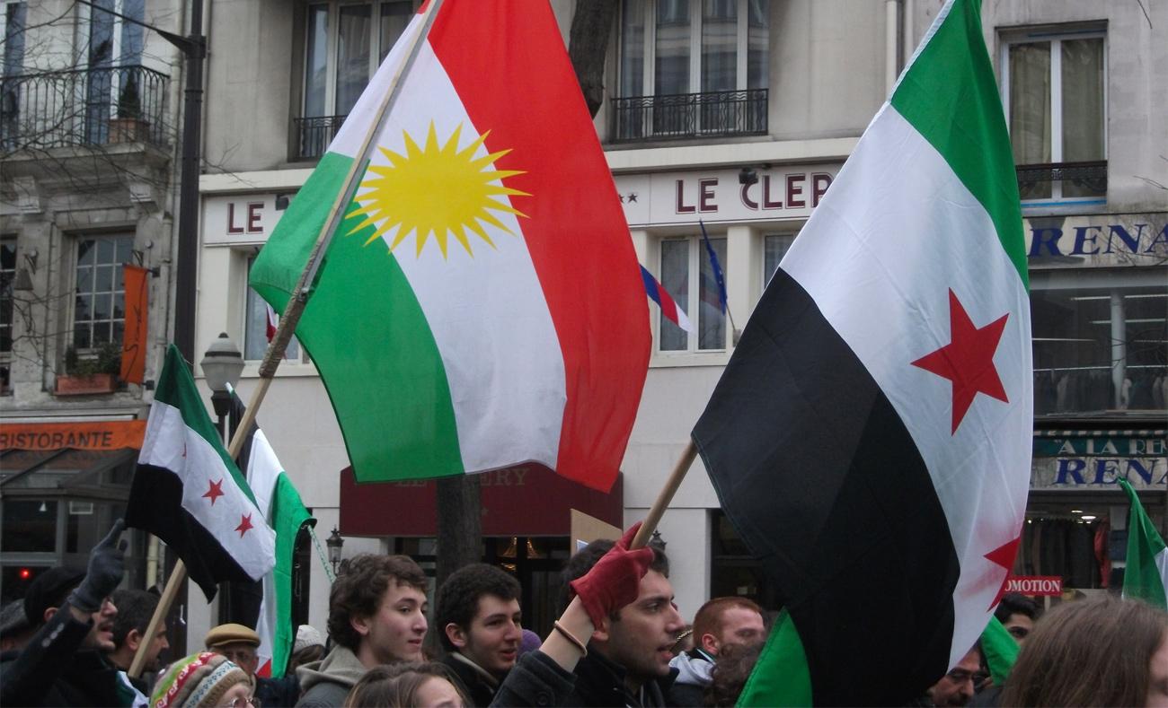 العلم الكردي بجانب علم الثورة السورية في مظاهرة معارضة للنصام السوري في باريس - آذار 2013 ( Association of World Citizens)