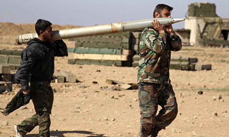 عناصران من قوات الأسد يحملان صاروخ غراد على الحبهات العسكرية في ريف الرقة الجنوبي - (انترنت)