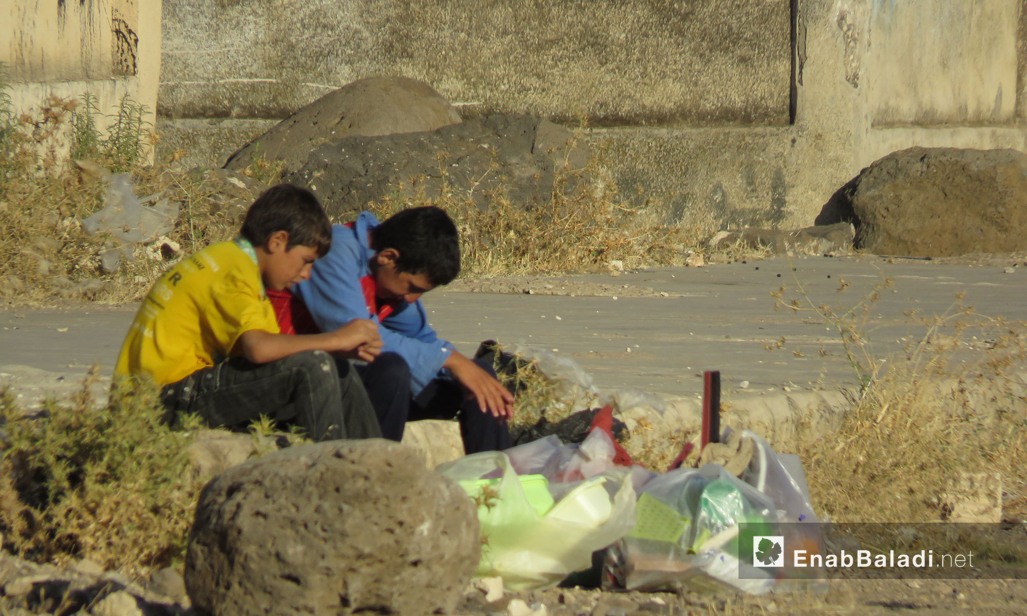أطفال يجلسون على قارعة الطريق في أحد أحياء الحولة بريف حمص - 25 تموز 2017 (عنب بلدي)