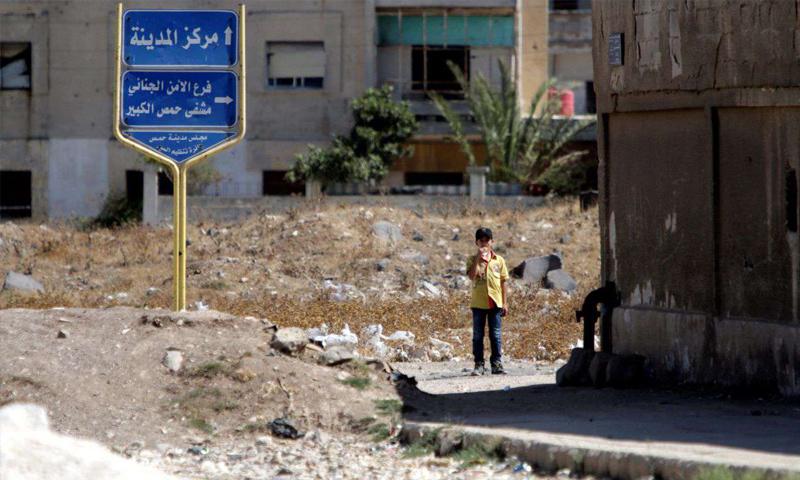 طفل يقف قرب لافتة طرقية في مركز مدينة حمص وسط سوريا - (رويترز)