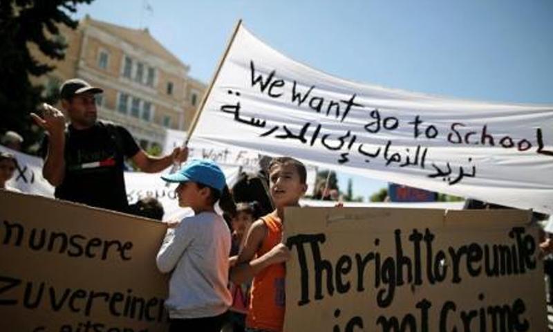 أطفال لاجئون سوريون في مسيرة للم شملهم مع ذويهم بأثينا - الأربعاء 2 آب - (رويترز)