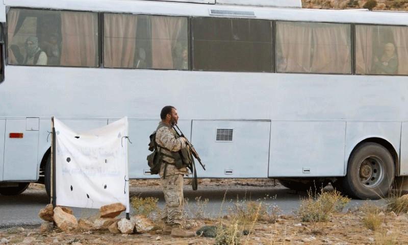 """مقاتل من """"حزب الله"""" اللبناني إلى جانب حافلات إخلاء المقاتلين في جرود عرسال - 2 آب 2017 (Reuters)"""