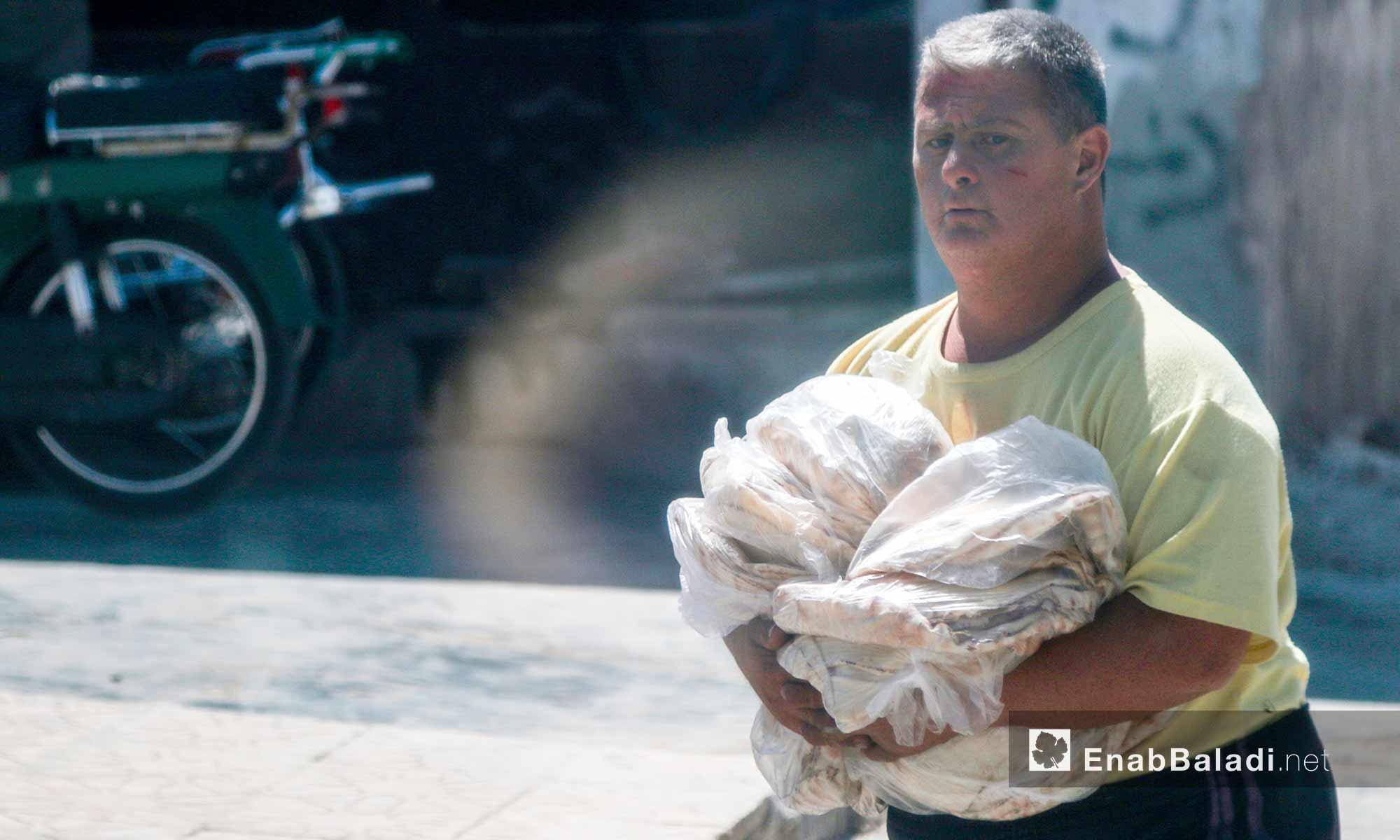 أحد سكان الأتارب يحمل الخبز ويتجه إلى بيته - 3 آب 2017 (عنب بلدي)