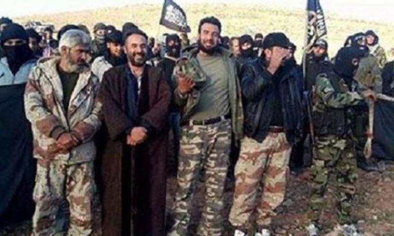 أمير تنظيم الدولة في القلمون الغربي يتوسط مجموعة من مقاتلي التنظيم في القلمون الغربي - (انترنت)
