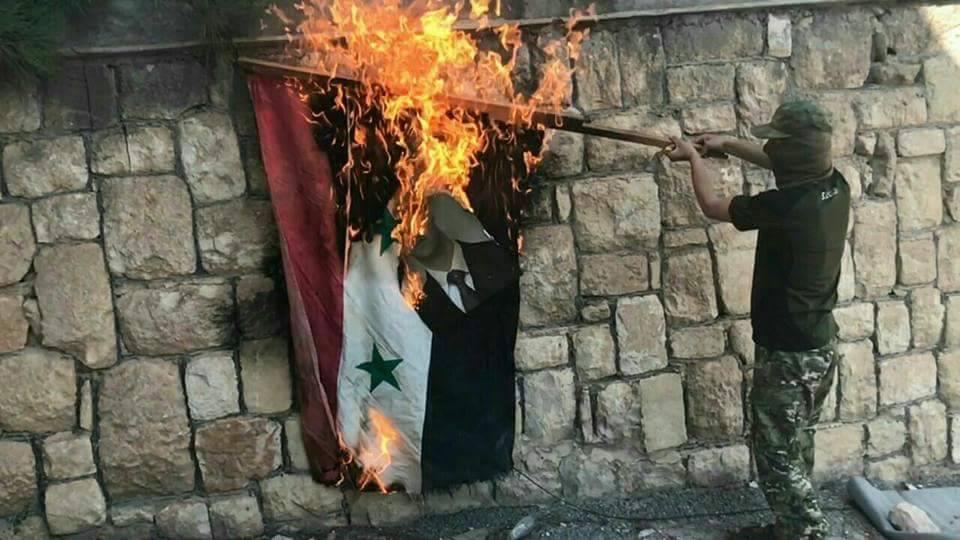 مقاتل من المعارضة يُحرق علم النظام السوري داخل قصر المخرم شرقي حماة - 19 أيلول 2017 (فيس بوك)