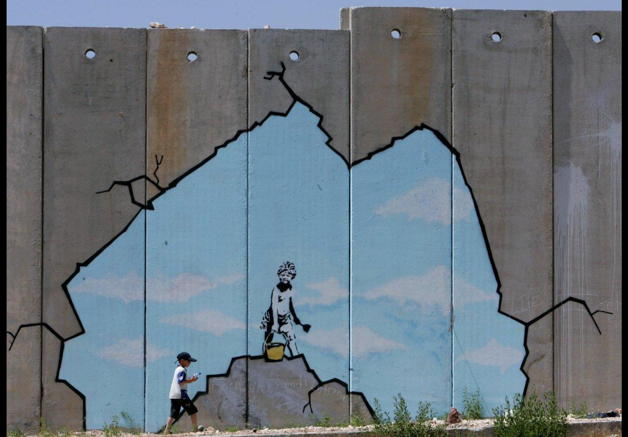 غرافيتي لبانكسي على جدار الفصل الإسرائيلي في فلسطين (رويترز)