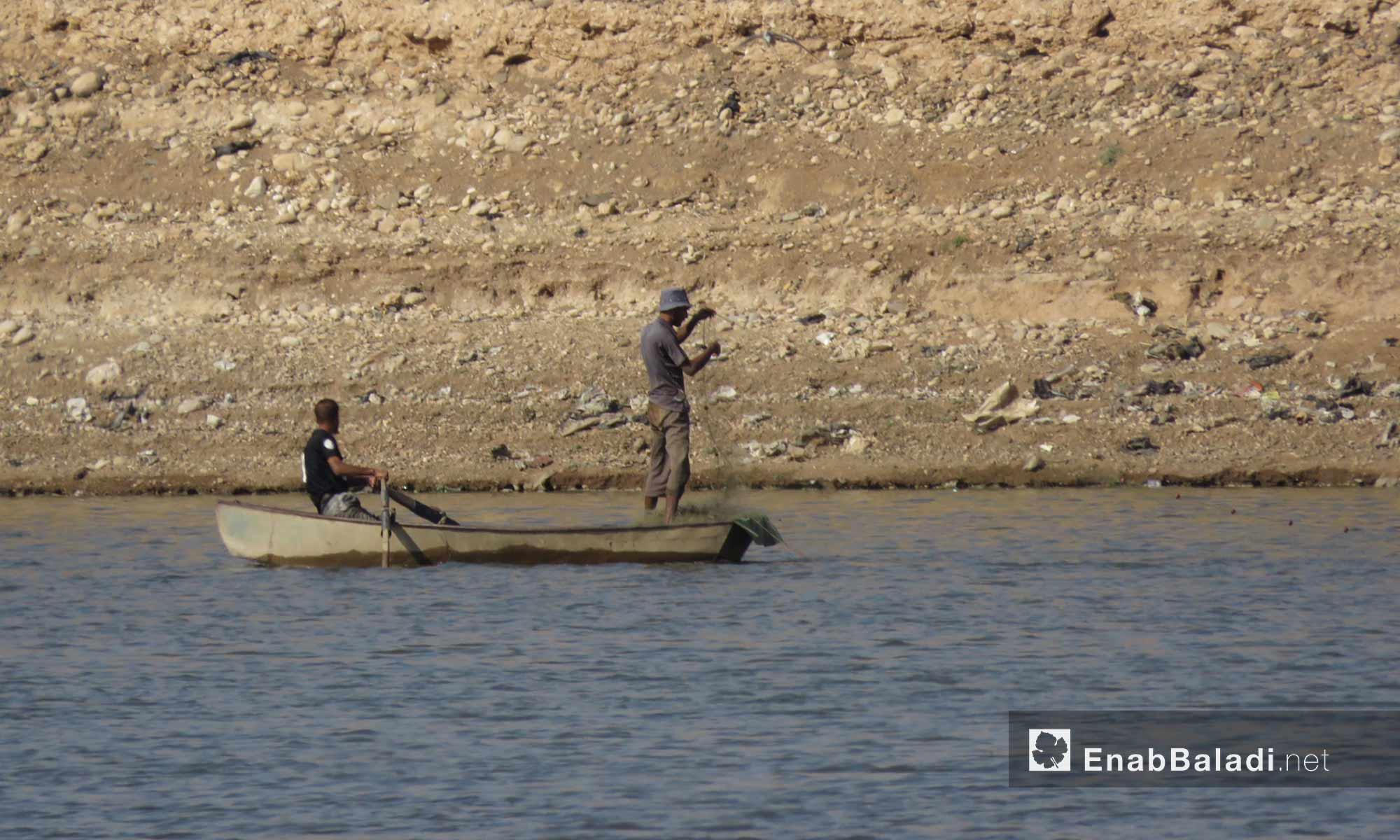 صيادان على متن قارب في بحيرة سد الرستن في ريف حمص الشمالي - 9 أيلول 2017 (عنب بلدي)