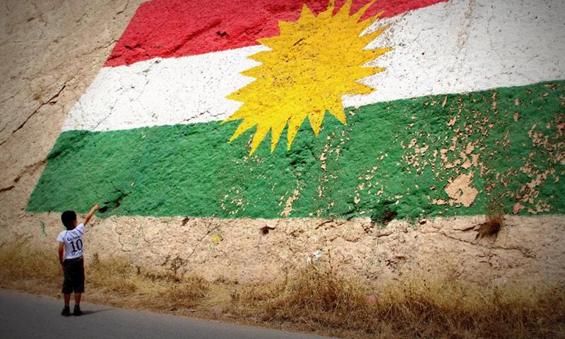 """طفل كردي يشير إلى علم """"كردستان"""" في العراق (إنترنت)"""