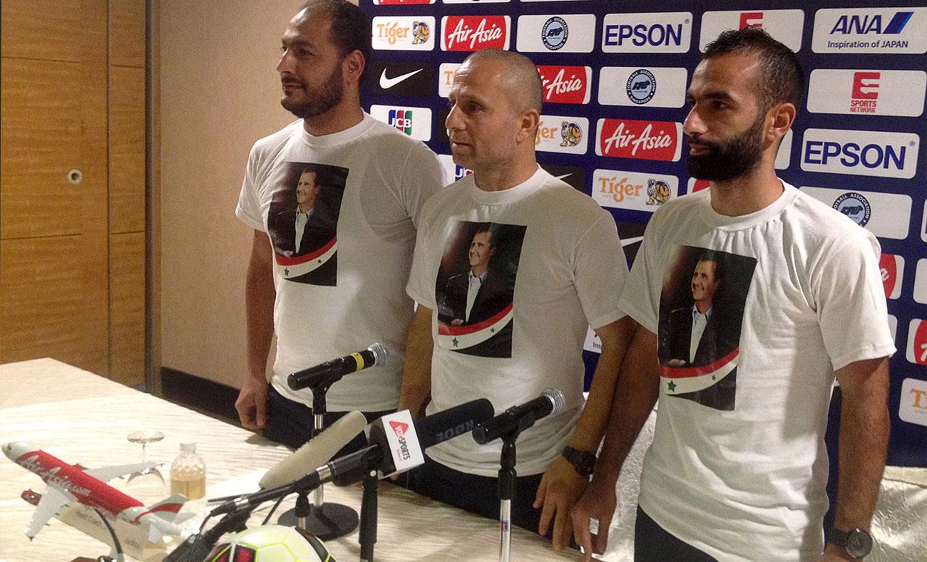 مدرب المنتخب السوري السابق فجر إبراهيم واللاعب أسامة أومري والإداري محمد بشار يحملون صور الأسد على قمصانهم في مؤتمر في سنغافورة عام 2015 (مؤتمر صحفي)