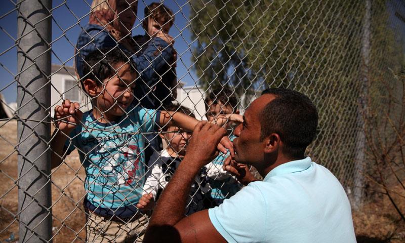 لاجئ سوري يعيش في قبرص يقبل أيدي اطفاله بعد وصولهم إلى مخيم للاجئين - 13 أيلول 2017 (رويترز)