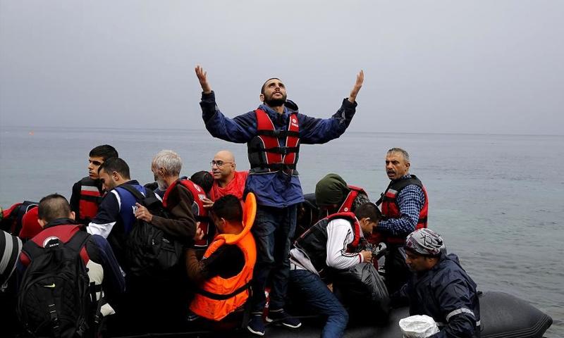 لاجئ سوري يشكر الله عند وصوله إلى جزيرة ليسبوس اليونانية مع مجموعة من اللاجئين - 23 كانون الأول 2016 (رويترز)