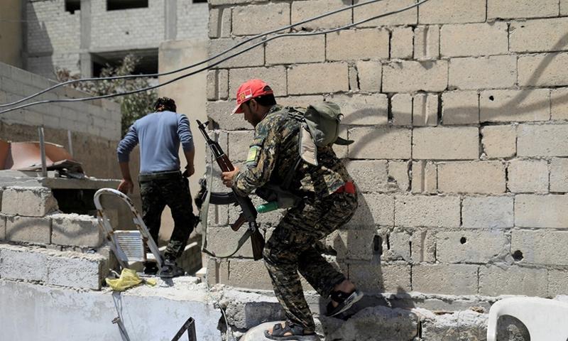 عناصر من قوات سوريا الديموقراطية خلال المواجهات العسكرية في الرقة - حزيران 2017 (رويترز)