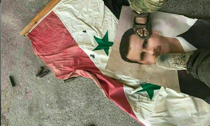 مقاتلان من المعارضة يدوسان صورة الأسد وعلم النظام السوري داخل قصر المخرم شرقي حماة - 19 أيلول 2017 (فيس بوك)