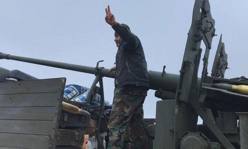 مقاتل من قوات الأسد يعتلي مدفع ثقيل خلال المعارك الدائرة ضد تنظيم الدولة الإسلامية في دير الزور - آب 2017 (AFP)
