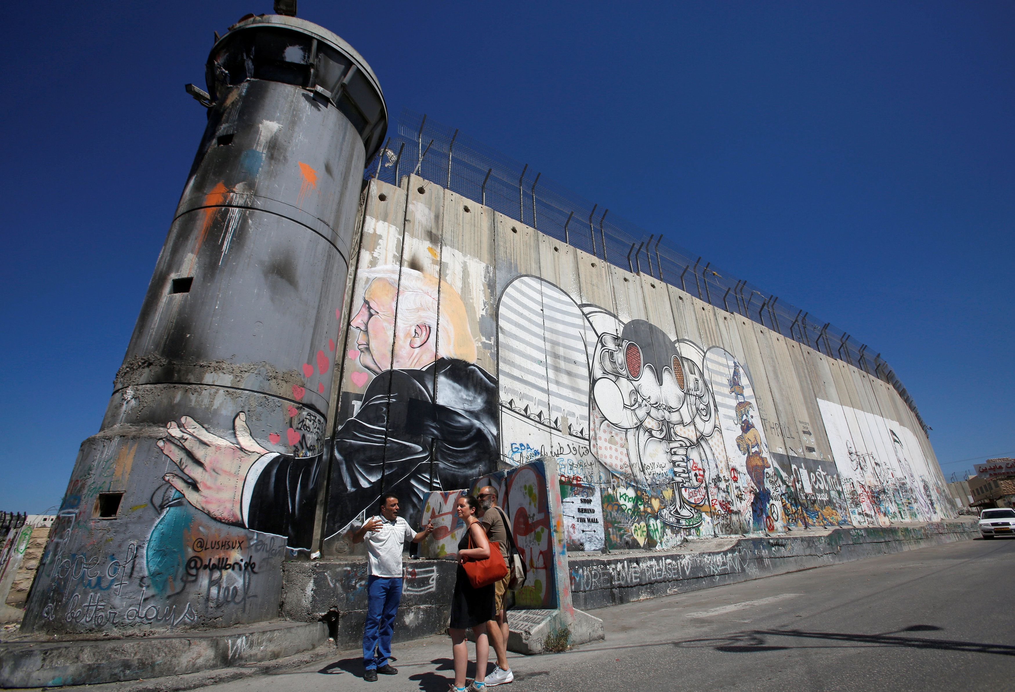 سياح يقفون أمام جرافيتي يصور الرئيس الأمريكي، دونالد ترامب، على جدار الفصل - 4 آب 2017 (رويترز)