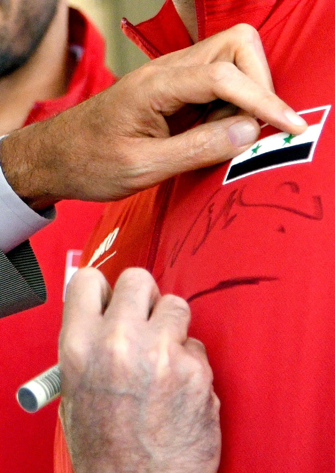 رئيس النظام السوري، بشار الأسد، يكتب اسمه على صدور لاعبي المنتخب السوري - 23 تشرين الأول 2017 (رئاسة الجمهورية)