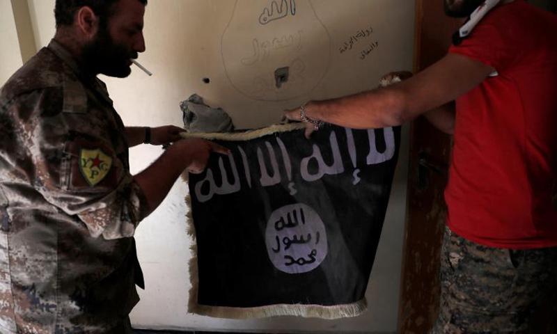 عناصر من قوات سوريا الديموقراطية يمسكون براية تنظيم الدولة في بناء داخل مدينة الرقة - أيلول 2017 (رويترز)
