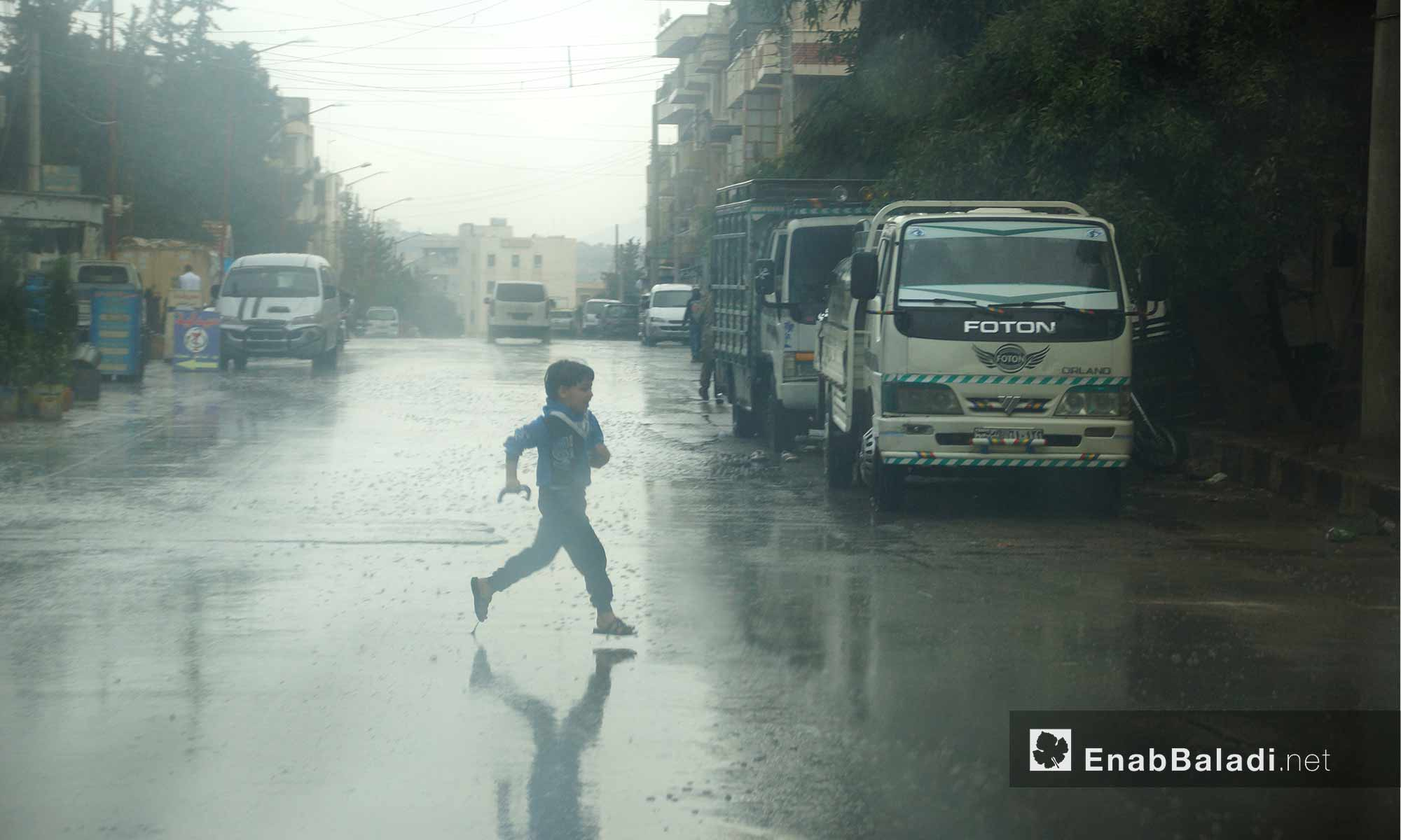 طفل يركض تحت المطر في مدينة إدلب - 9 تشرين الأول 2017 (عنب بلدي)