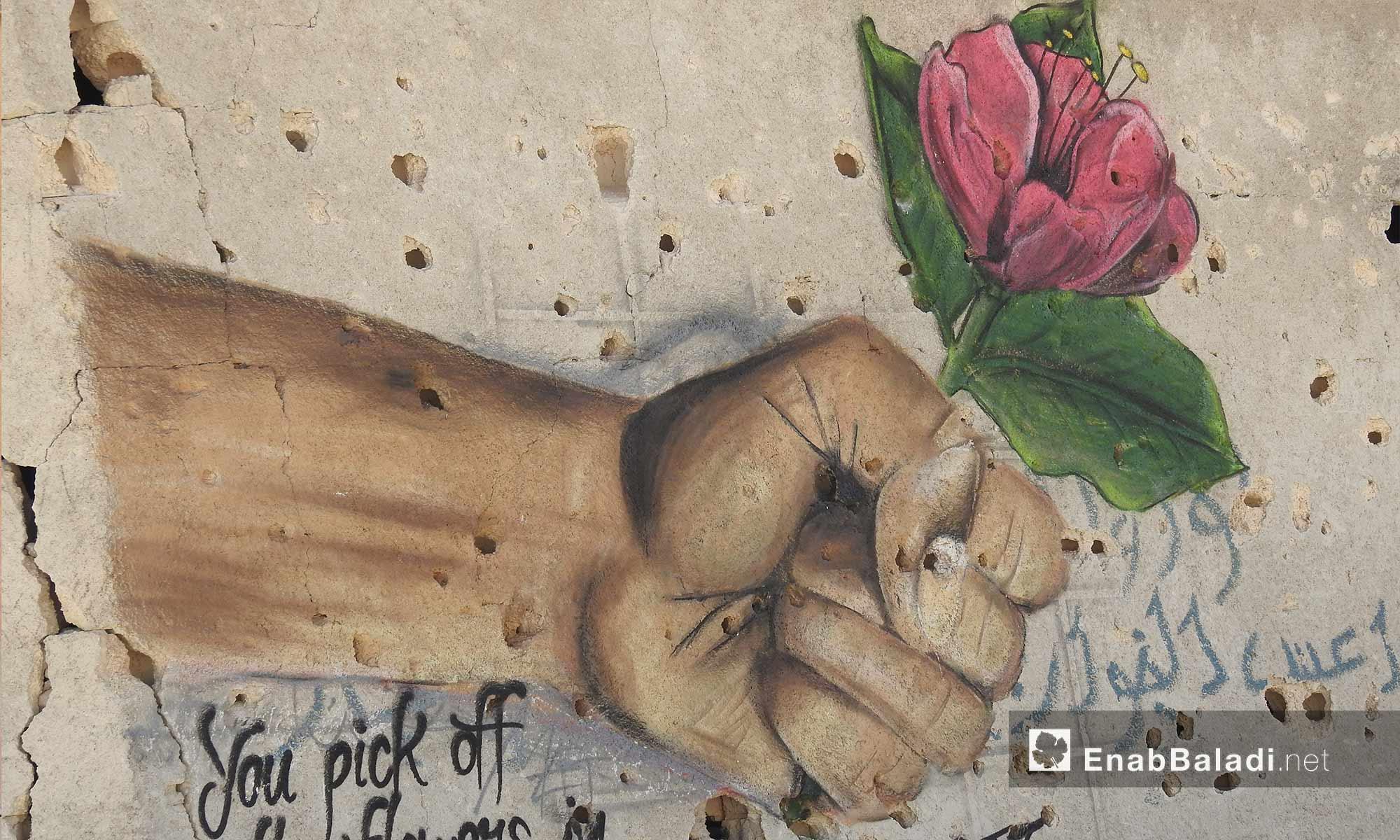 رسم غرافيتي ليد تحمل وردة على جدران مهدمة في قرية براغيدة بريف حلب الشمالي - 2 تشرين الأول 2017 (عنب بلدي)