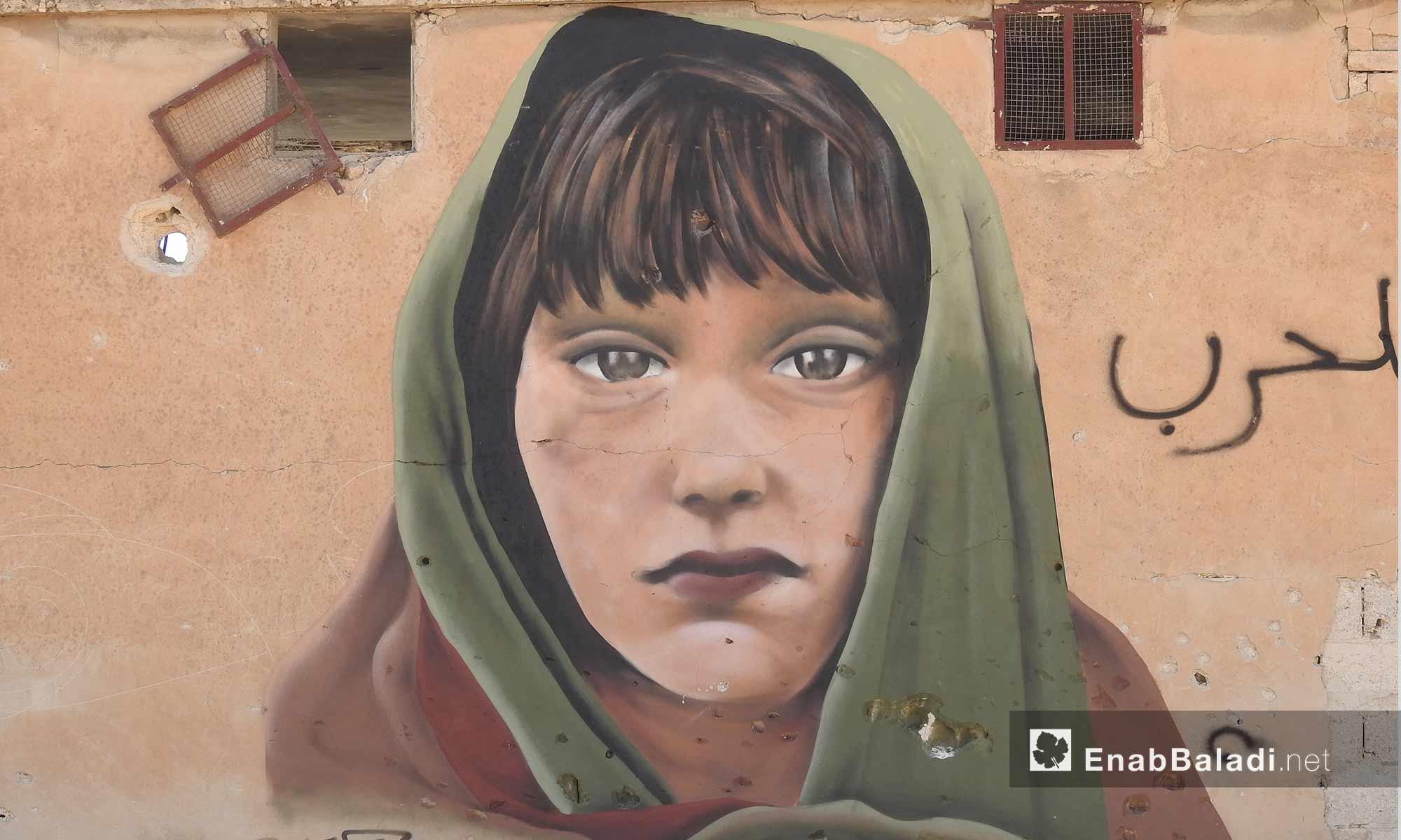 رسم غرافيتي لطفلة على جدران مهدمة في قرية براغيدة بريف حلب الشمالي - 2 تشرين الأول 2017 (عنب بلدي)