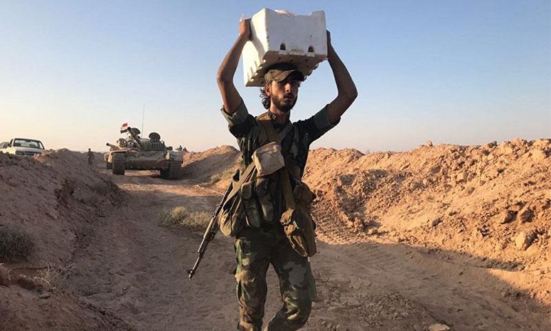 عنصر من قوات الأسد يحمل مواد غذائية أثناء العمليات العسسكرية في درير الزور - 15 أيلول 2017 - (سبوتنيك)