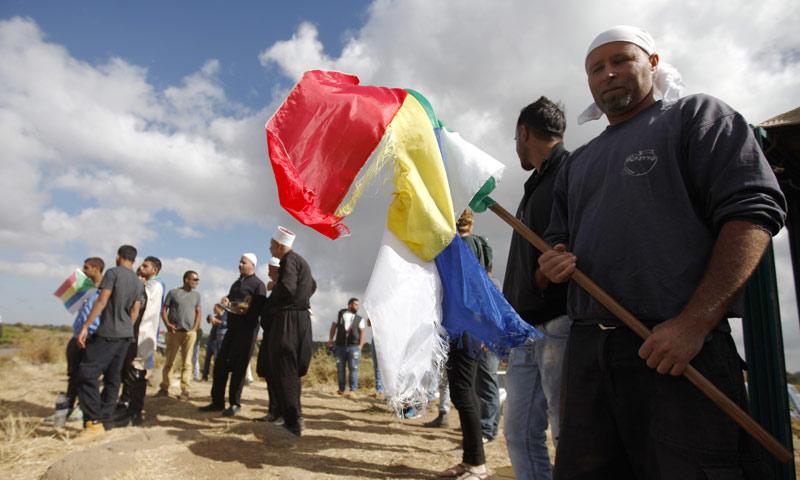 مجموعة من أبناء السويداء يرفعون راية الدروز في ريف المحافظة (AFP)