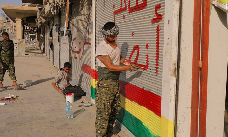 """مقاتلون من """"قسد"""" يلونون المحال التجارية في الرقة بعلم """"الوحدات"""" الكردية - 22 تشرين الأول 2017 (فيس بوك)"""