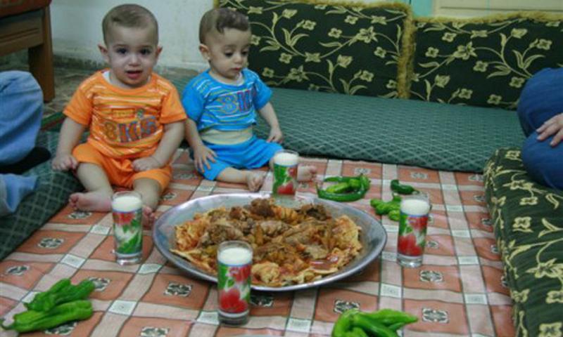 أطفال يتناولون الطعام في دير الزور (انترنت)