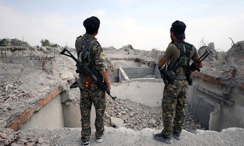 عناصر من قوات سوريا الديموقراطية يفقون فوق أبنية مدمرة في أحياء مدينة الرقة - أيلول 2017 (رويترز)