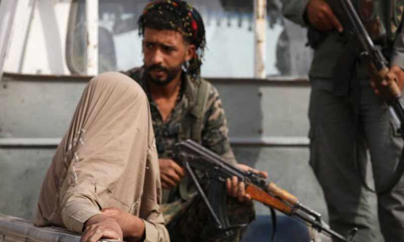 """تعبيرية: مقاتل من """"قسد"""" يعتقل رجلًا مصابًا خلال القتال مع تنظيم """"الدولة الإسلامية"""" - 24 أيلول 2017 (Reuters)"""