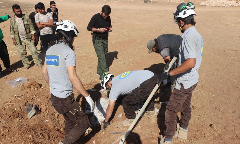 """عناصر """"الدفاع المدني"""" ينتشلون جثثًا من مقبرة جماعية شمالي حلب - 22 تشرين الأول 2017 (مديرية الدفاع المدني في حلب الحرة)"""
