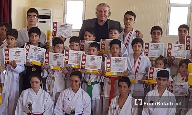 الناطق باسم الهيئة الرياضية، عروة قنواتي، وأطفال سوريون يحملون شهادات كاراتية في عنتاب التركية - 7 تشرين الأول 2017 (عنب بلدي)