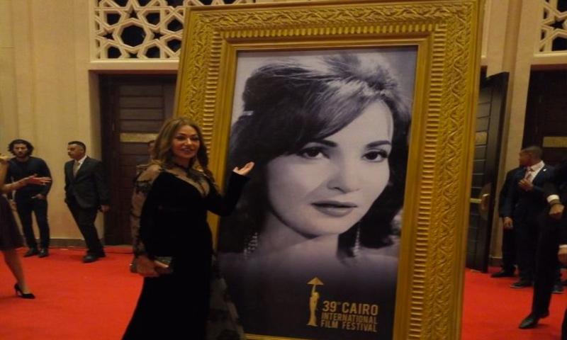 الممثلة المصرية ليلى علوي أمام صورة تكريمية للفنانة شادية (إنترنت)