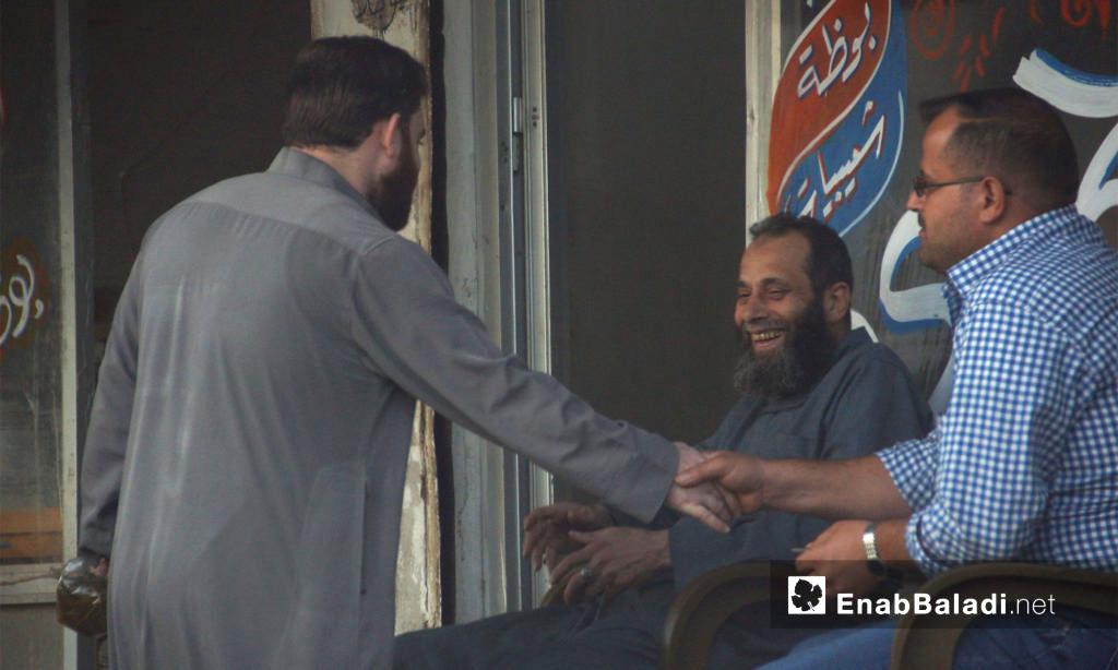 رجال يتبادلون الحديث أمام أحد المحلات في إدلب المدينة - 21 تشرين الأول 2017 (عنب بلدي)