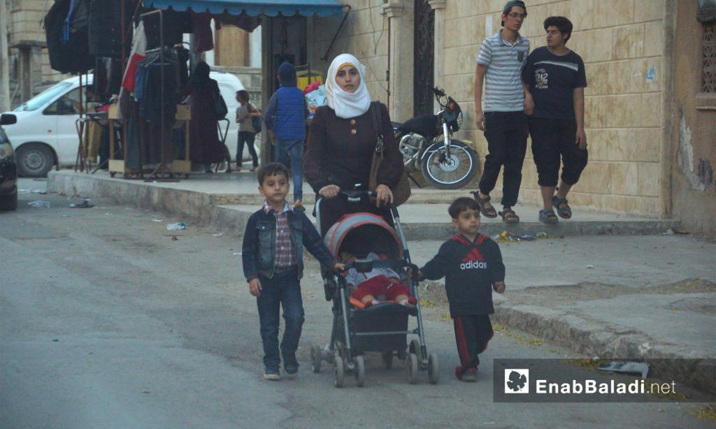 امرأة تتجول مع أطفالها في سوق مدينة إدلب - 21 تشرين الأول 2017 (عنب بلدي)