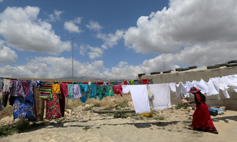 امرأة سورية تعلق الملابس في مخيم بر إلياس في البقاع اللبناني - 20 حزيران 2015 (Jamal Saidi)