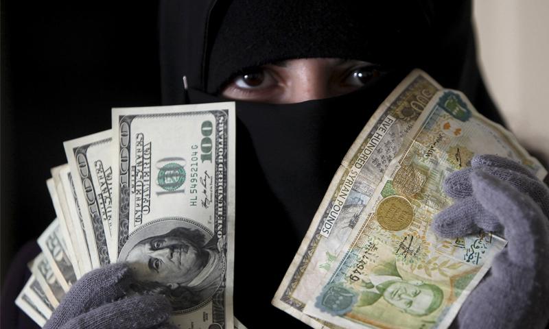 امرأة تحمل عملة سورية مقابل الدولار في العاصمة الأردنية عمان (رويترز)